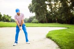 采取地堡射击的高尔夫球运动员 库存图片