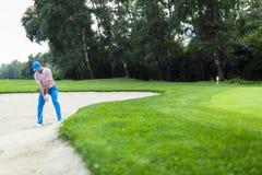 采取地堡射击的高尔夫球运动员 免版税库存图片