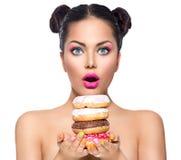采取堆五颜六色的油炸圈饼的秀丽女孩 免版税图库摄影