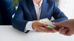 采取堆金钱的商人特写镜头照片作为贿款 库存图片