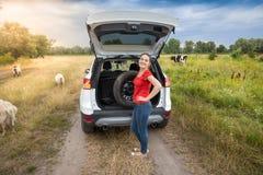 采取备用轮胎的少妇在乡下路的车厢外面 免版税图库摄影