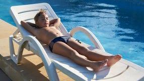 采取太阳的逗人喜爱的男孩在游泳池附近 库存图片