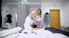 采取女性客户的测量的成熟裁缝使用磁带在工作室 剪裁的演播室工作两名妇女 股票视频