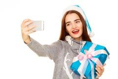 采取她在白色的温暖的毛线衣的年轻愉快的妇女selfie 免版税图库摄影