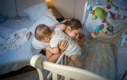 采取她的小儿子的年轻母亲在小儿床外面在晚上 免版税库存图片