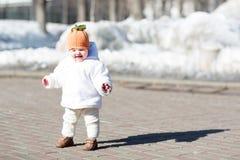 采取她的第一步的小婴孩在晴天 免版税库存图片
