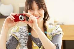 采取妇女年轻人的照相机数字式照片 免版税图库摄影