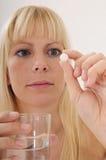 采取妇女的白肤金发的药片 库存照片