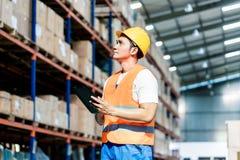 采取存货的工作者在仓库里 免版税库存照片