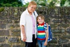 采取孩子,学校的孩子男孩的祖母在他的第一天 免版税库存照片