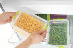 采取容器用从冰箱的冷冻玉米的妇女 库存图片