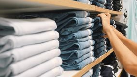 采取对从堆的蓝色牛仔布牛仔裤的年轻女人在衣物商店 选择在购物的女性手正确裤子大小 股票录像