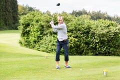 采取射击的男性高尔夫球运动员 免版税库存照片