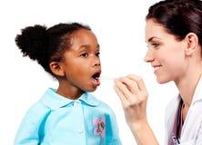 采取小女孩的温度的微笑的医生 库存图片