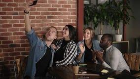 采取小组selfie的白种人人在会见不同的朋友在coffeeshop或工作场所,多种族正面年轻 股票录像