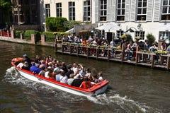 采取小船旅行的游人在布鲁日游览 库存照片