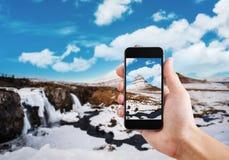 采取山Kirkjufell风景在冬天由流动巧妙的电话 免版税库存图片