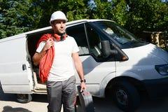 采取工具的年轻电工工匠在专业卡车搬运车外面 免版税库存图片