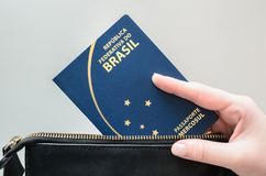 采取巴西护照的妇女手在袋子外面 图库摄影