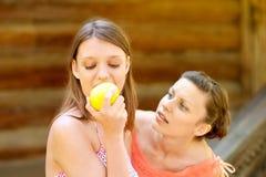 采取年轻人的苹果美丽的叮咬女孩 免版税库存图片