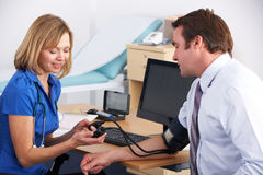 采取患者的血压的英国医生 免版税库存照片