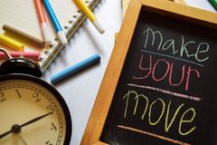 采取您的行动在词组五颜六色手写在黑板、闹钟以刺激和教育概念 免版税库存照片