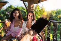 采取数字式从男性手的两名愉快的微笑的妇女片剂个人计算机,当食用在夏天大阳台的早餐一起时 免版税库存图片