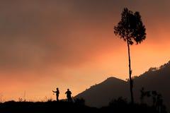 采取日落的射击夫妇使用handphone和照相机 免版税图库摄影