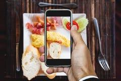 采取早餐煎蛋卷食物,顶视图由流动巧妙的电话 库存图片