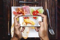 采取早餐煎蛋卷食物,顶视图由流动巧妙的电话 免版税库存图片