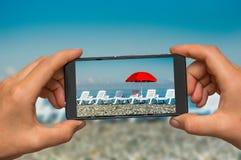 采取晒日光浴的床照片和有电话的红色伞 免版税图库摄影