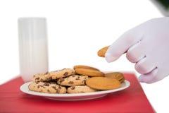 采取曲奇饼的圣诞老人的手 免版税库存图片