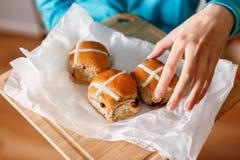 采取有十字架形的圆形圣糕的手 免版税图库摄影