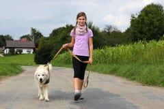 采取步行的女孩一条狗 图库摄影