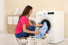 采取洗衣店的年轻女人在洗衣机外面 库存图片
