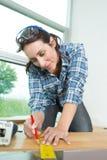 采取测量委员会的女性木匠 库存照片