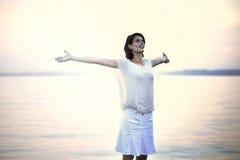 采取深呼吸的愉快的妇女在日落 免版税库存照片