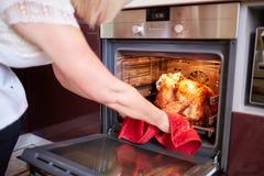 采取火鸡的妇女在厨房背景的烤箱外面 烤,传统火鸡烹调 圣诞节构成文件高分辨率被掀动的火鸡非常 免版税库存照片