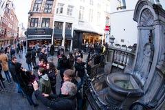 采取照片和selfies的游人在Manneken Pis 免版税图库摄影
