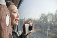 采取照片外部火车窗口的少妇 免版税库存图片