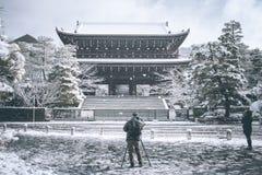 采取照片有她的智能手机和他的数字照相机的妇女和人日本寺庙 图库摄影