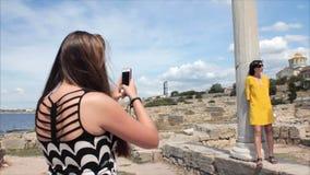 采取照片有智能手机的愉快的妇女女朋友在古城背景的废墟 股票录像