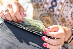 采取现金的妇女在钱包外面 库存图片