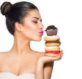 采取甜点和五颜六色的油炸圈饼的女孩 免版税库存照片