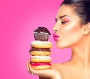 采取甜点和五颜六色的油炸圈饼的女孩 库存照片