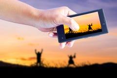 采取生动描述孩子使用在日落、剪影、自由和幸福 免版税库存图片