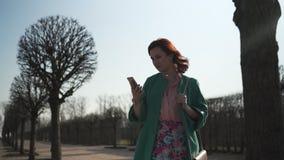 采取电话的少女出于口袋和文本穿着绿色时尚夹克和五颜六色的裙子的消息 股票视频