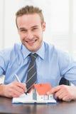 采取笔记和拿着的微笑的商人微型家 免版税库存照片