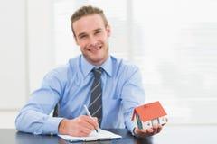 采取笔记和显示微型房子的商人 库存照片