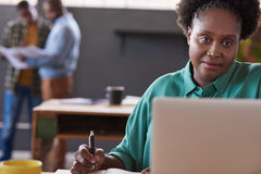 采取笔记和研究膝上型计算机的被聚焦的非洲女实业家 库存图片